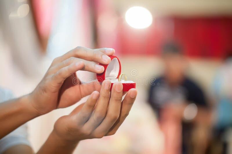 Caja roja a mostrar, anillo de bodas del control de la mano del ` s del novio Símbolos de la boda y de la boda fotos de archivo libres de regalías