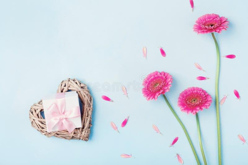 Caja rosada de las flores, del corazón y de regalo del gerbera en la opinión de sobremesa azul Tarjeta de felicitación para el dí imagen de archivo