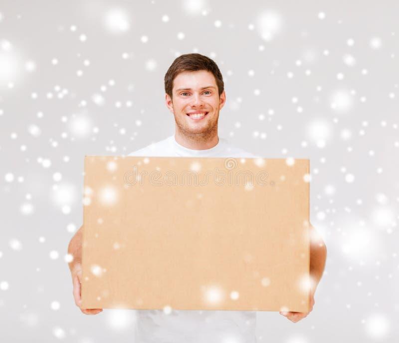 Caja sonriente del cartón del hombre que lleva foto de archivo libre de regalías