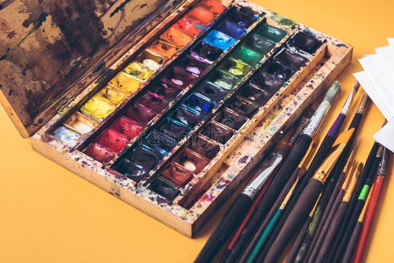 Caja sucia de pinturas y de brochas de la acuarela en el lugar de trabajo del diseñador fotografía de archivo