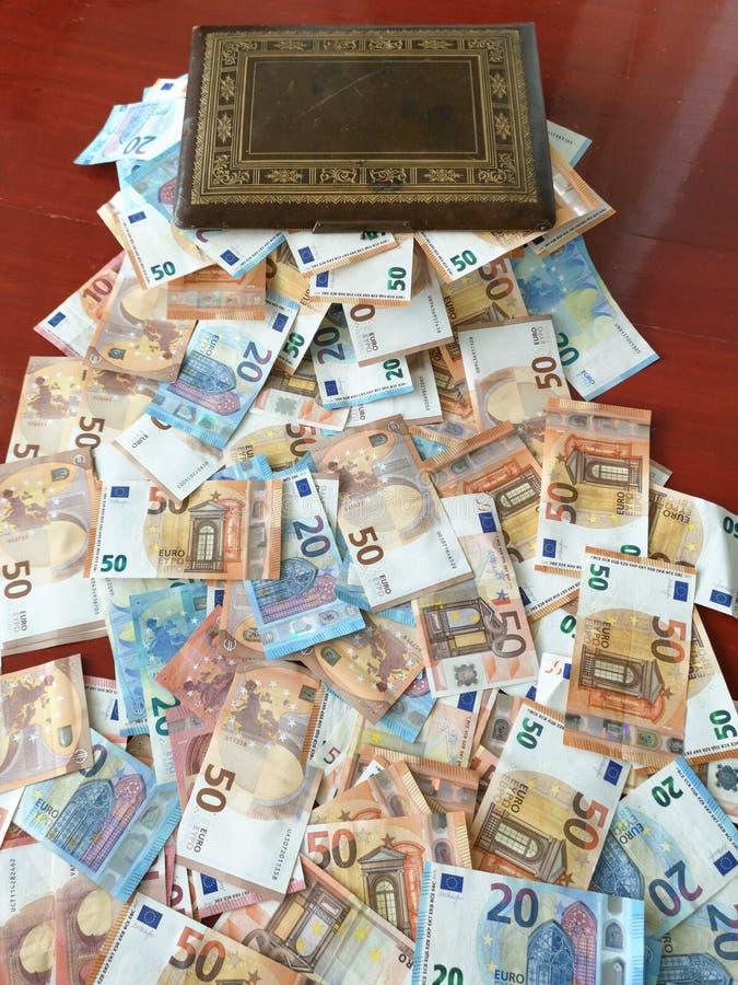 Caja vieja mágica que desborda con los billetes de banco euro, el dinero europeo cuentas de cincuenta y veinte euros fotos de archivo libres de regalías