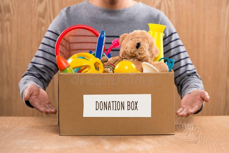 Caja voluntaria de la donación del varón que se sostiene con los juguetes viejos fotos de archivo