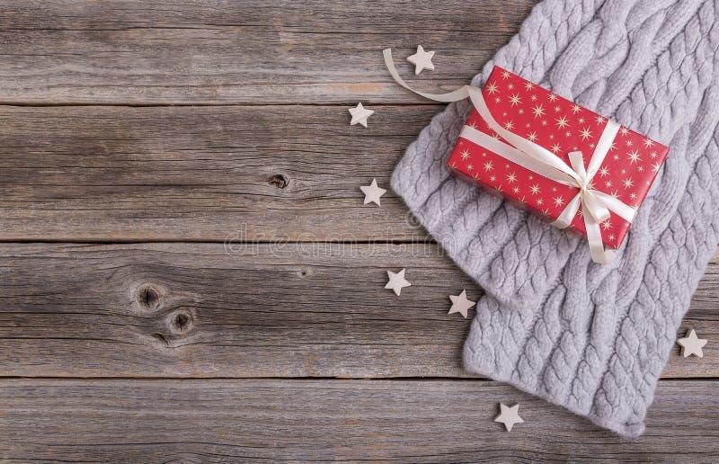 Caja y bufanda de regalo en los tableros de madera fotografía de archivo