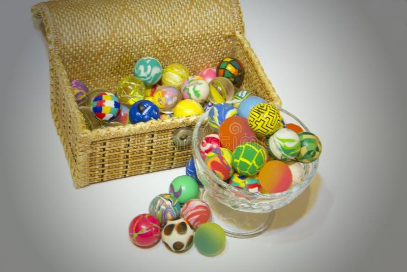 Caja y de cristal por completo de bolas coloridas imagen de archivo
