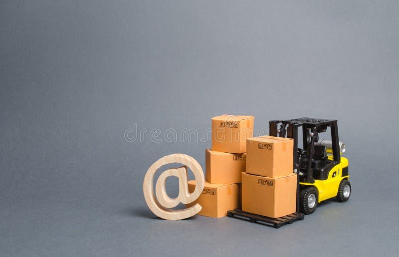 Cajas amarillas de la carretilla elevadora y de cartón y símbolo del correo electrónico comercial EN Comercio electr?nico ventas  imagen de archivo libre de regalías
