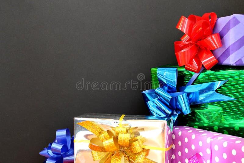 Cajas brillantes mucho regalo por un día de fiesta en un fondo negro imágenes de archivo libres de regalías