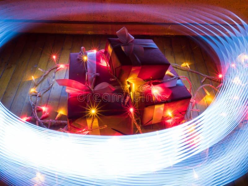 Cajas con los regalos de la Navidad con las guirnaldas con las lámparas y rastros de la pintura por la luz azul imagen de archivo