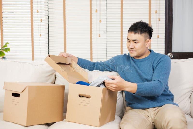 Cajas de cartón abiertas del hombre asiático mientras que se mueve al nuevo hogar en el sofá en sala de estar desempaque para la  fotos de archivo