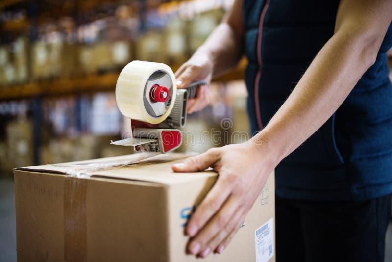 Cajas de cartón masculinas del lacre del trabajador del almacén fotos de archivo libres de regalías