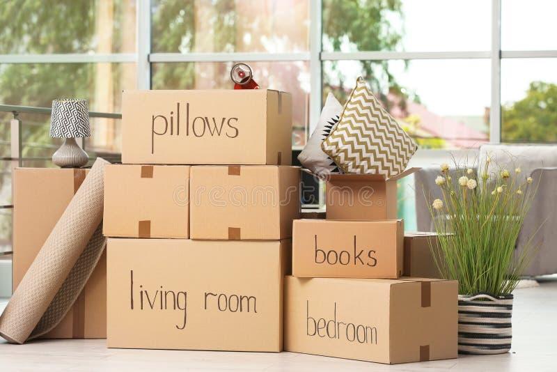Cajas de cartón y materia de hogar dentro imágenes de archivo libres de regalías