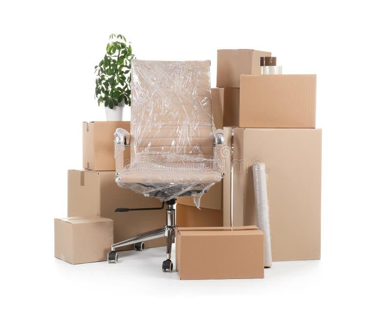 Cajas de cartón y materia de hogar en el fondo blanco fotografía de archivo