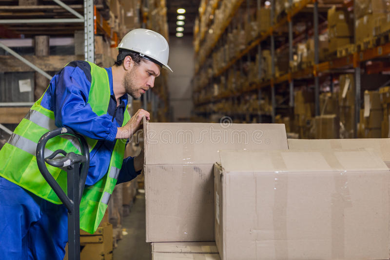 Cajas de comprobación del trabajador con mercancía en almacén foto de archivo libre de regalías