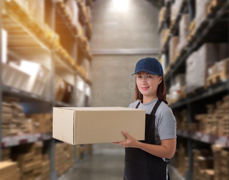 Cajas de elevaci?n del paquete del personal femenino en el almac?n fotos de archivo libres de regalías