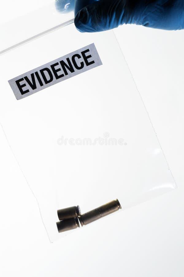Cajas de la bala en el bolso de las pruebas sostenido por la mano con guantes del científico forense azul foto de archivo libre de regalías