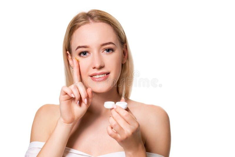 Cajas de lentes de contacto de la tenencia de la mujer joven y lente delante de su cara en el fondo blanco fotos de archivo libres de regalías