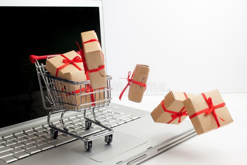 Cajas de papel en un carro de la compra en un teclado del ordenador portátil Ideas sobre comercio electrónico, una transacción de foto de archivo libre de regalías
