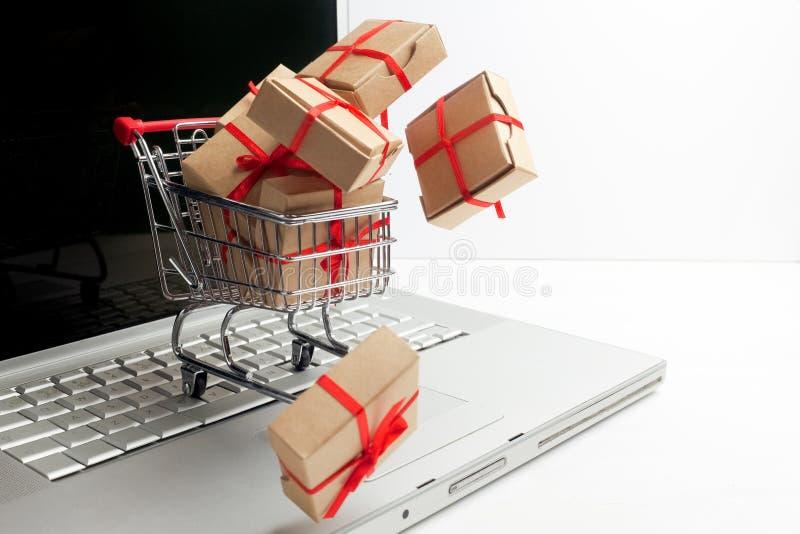Cajas de papel en un carro de la compra en un teclado del ordenador portátil Ideas sobre comercio electrónico, una transacción de fotos de archivo