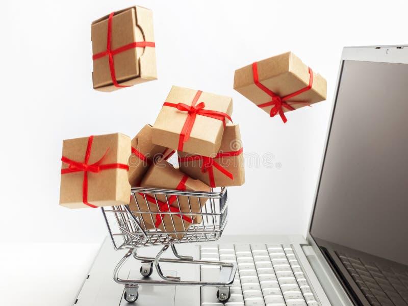 Cajas de papel en un carro de la compra en un teclado del ordenador portátil Ideas sobre comercio electrónico, una transacción de imagen de archivo libre de regalías