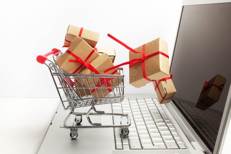 Cajas de papel en un carro de la compra en un teclado del ordenador portátil Ideas sobre comercio electrónico, una transacción de fotos de archivo libres de regalías