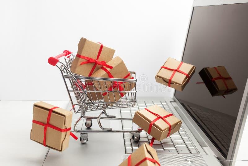 Cajas de papel en un carro de la compra en un teclado del ordenador portátil Ideas sobre comercio electrónico, una transacción de imagen de archivo