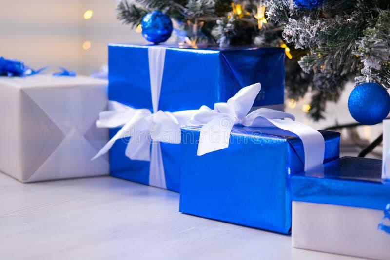 Cajas de regalo azules debajo del árbol de navidad Azul y blanco coloridos, cajas de regalo con el arco de la cinta fotos de archivo