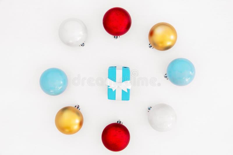 Cajas de regalo azules en colores pastel de Hristmas dentro del marco redondo hecho de bolas coloridas en el fondo blanco imagen de archivo