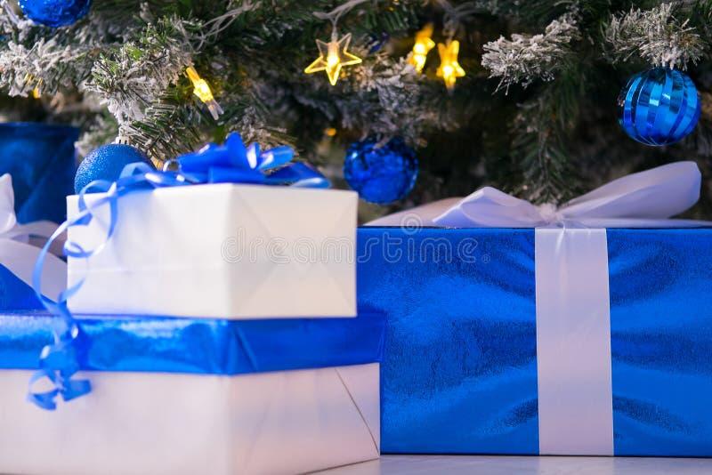 Cajas de regalo azules y blancas debajo del árbol de navidad Azul y blanco coloridos, cajas de regalo con el arco de la cinta fotografía de archivo libre de regalías