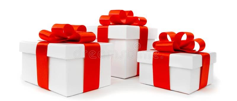 Cajas de regalo blancas con los arcos rojos de la cinta fotografía de archivo