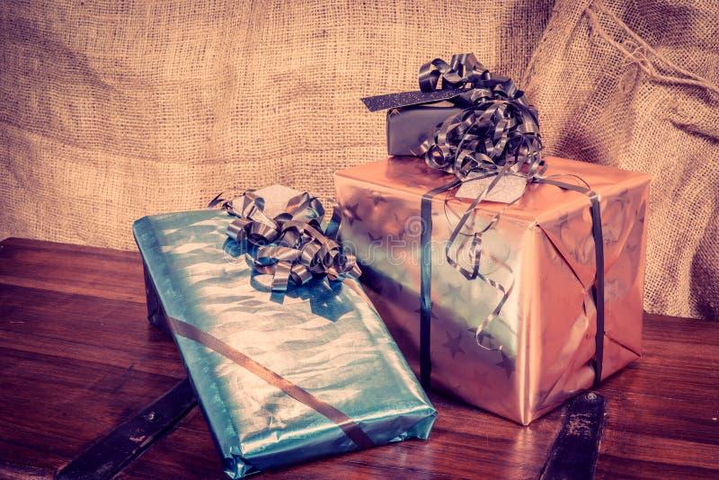 Cajas de regalo brillantes en una tabla de madera fotografía de archivo libre de regalías