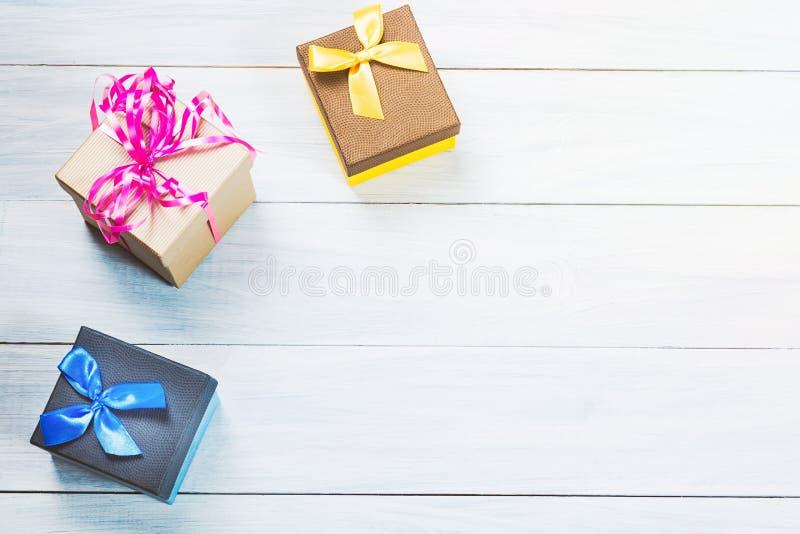 Cajas de regalo coloridas en fondo de madera blanco agradable con el espacio libre Puede ser utilizado para el día de tarjetas de fotografía de archivo