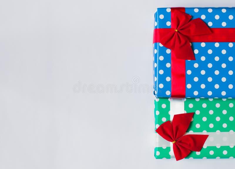 Cajas de regalo con la cinta roja y blanca y los arcos rojos, en el empaquetado azul y verde En el fondo blanco Copie el espacio fotografía de archivo