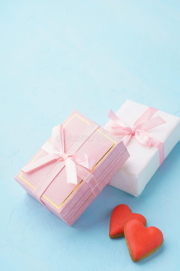 Cajas de regalo con la cinta rosada y las galletas en forma de corazón rojas imagen de archivo libre de regalías