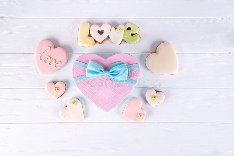 Cajas de regalo de día de San Valentín con las galletas en forma de corazón y decoraciones en el fondo de madera blanco Fondo del foto de archivo libre de regalías