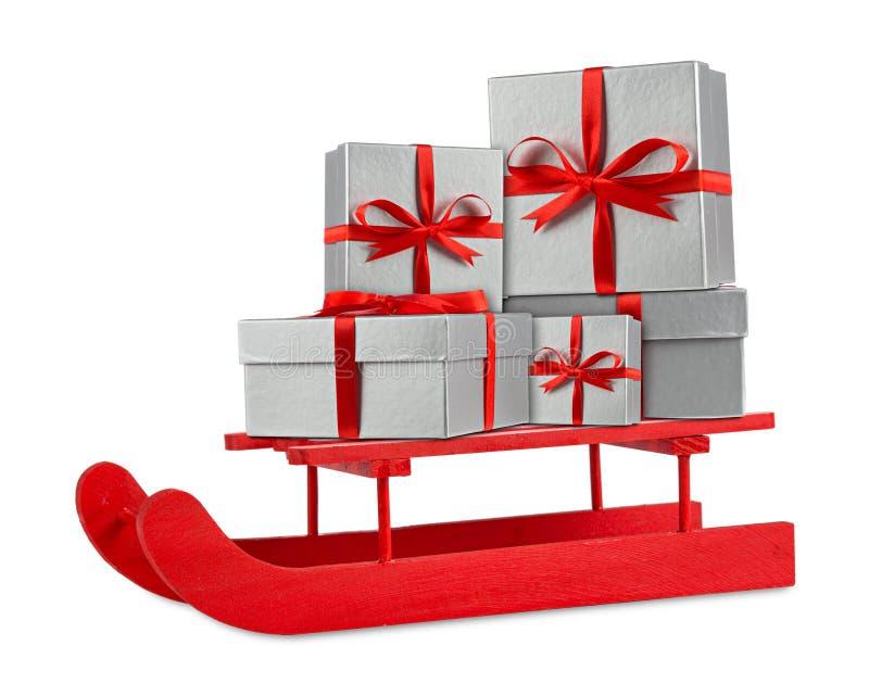 Cajas de regalo de plata rojas de la Navidad en el trineo de madera rojo de Papá Noel fotos de archivo libres de regalías