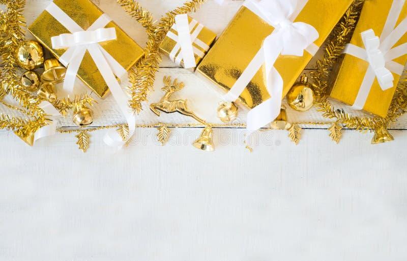 Cajas de regalo del oro y la Navidad que brilla que adornan artículos en el fondo de madera blanco del panel, diseño de la fronte foto de archivo