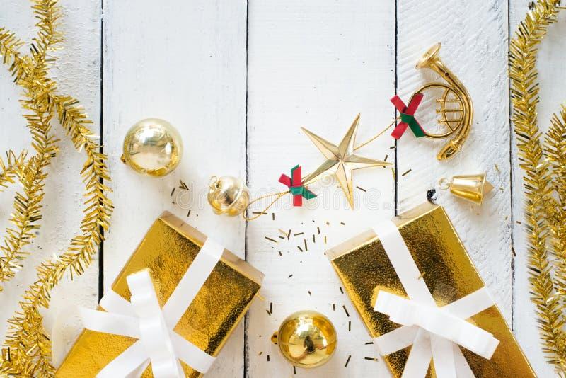 Cajas de regalo del oro y ornamentos de la Navidad en el fondo de madera blanco para la composición del marco del Año Nuevo, dise foto de archivo libre de regalías