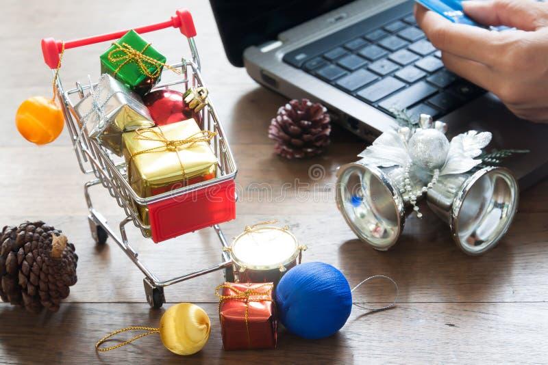 Cajas de regalo en carro de la compra y decoraciones de la Navidad, mujer que sostiene la tarjeta de crédito en el ordenador port imagen de archivo libre de regalías