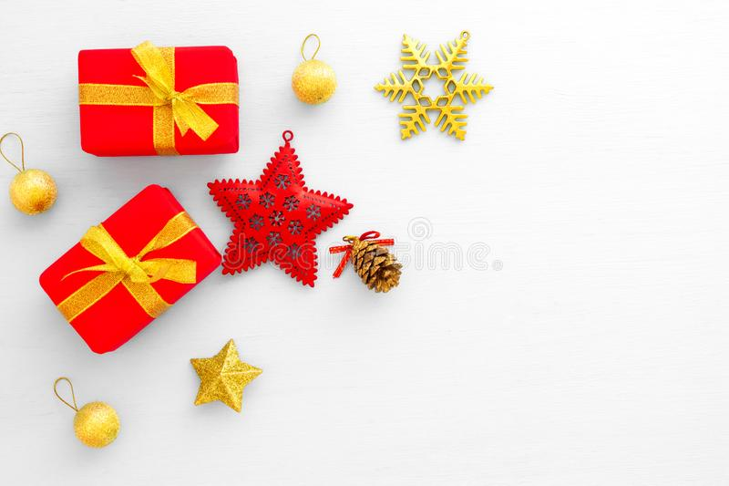 Cajas de regalo, estrella, bola del oro, cono del pino y copo de nieve rojos en el fondo blanco imágenes de archivo libres de regalías