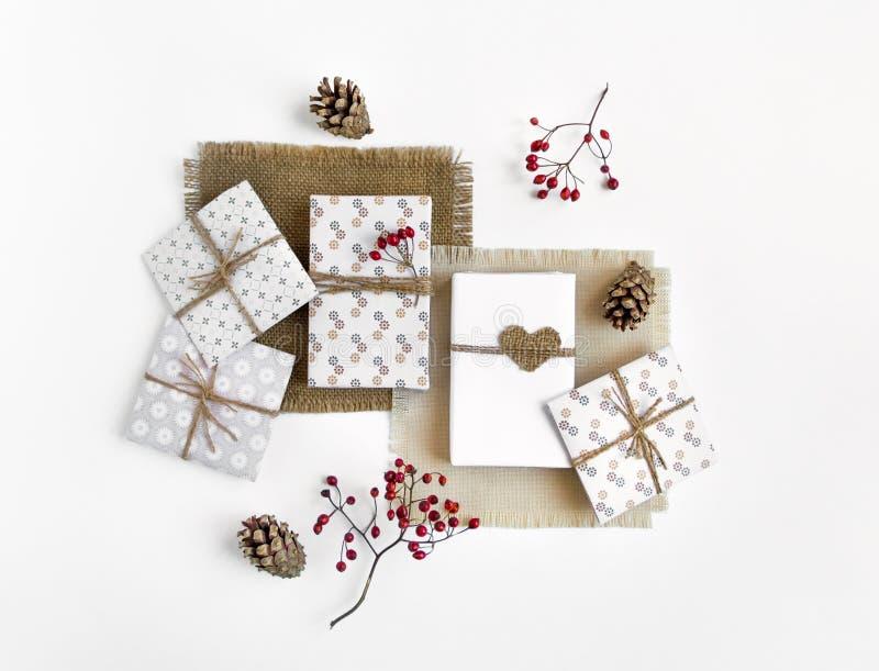 Cajas de regalo hechas a mano rústicas en el fondo blanco adornado con las bayas Visión superior, endecha plana foto de archivo