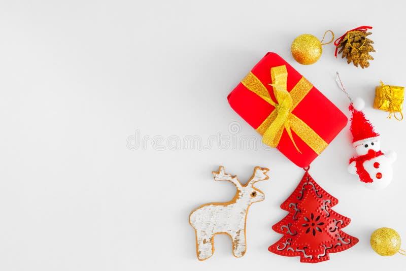 Cajas de regalo de la Navidad, árbol de abeto rojo, muñeco de nieve, reno, bolas del oro y cono del pino en el fondo blanco foto de archivo