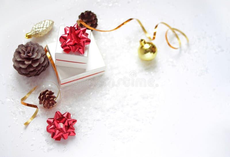 Cajas de regalo de la Navidad con un arco rojo, una bola de la Navidad, una cinta de oro, conos en un fondo blanco con nieve y lu imagenes de archivo