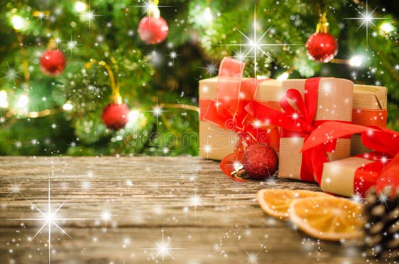 Cajas de regalo de la Navidad contra la perspectiva del árbol de navidad y del bokeh de las luces del partido que centellean imagenes de archivo