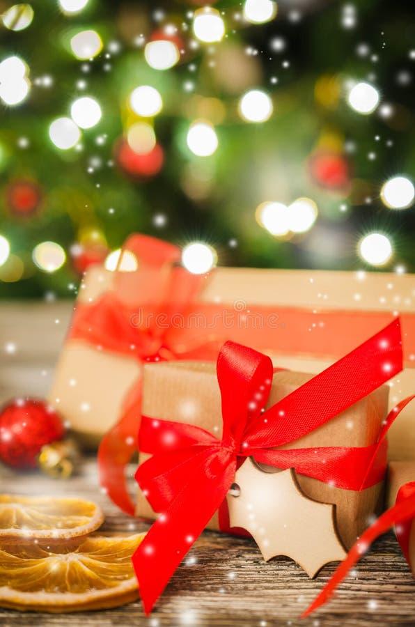 Cajas de regalo de la Navidad contra la perspectiva del árbol de navidad y del bokeh de las luces del partido que centellean fotos de archivo libres de regalías