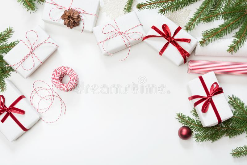 Cajas de regalo de la Navidad envueltas en el documento blanco del arte y la cinta decorativa de la cuerda roja sobre la superfic fotografía de archivo