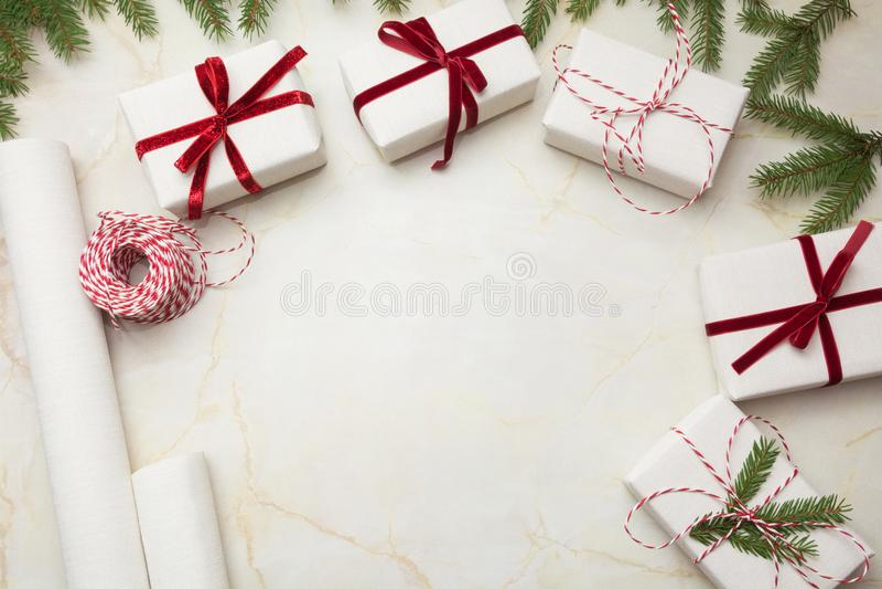 Cajas de regalo de la Navidad envueltas en el documento blanco del arte y la cinta roja decorativa sobre superficie marmórea Ende imagenes de archivo