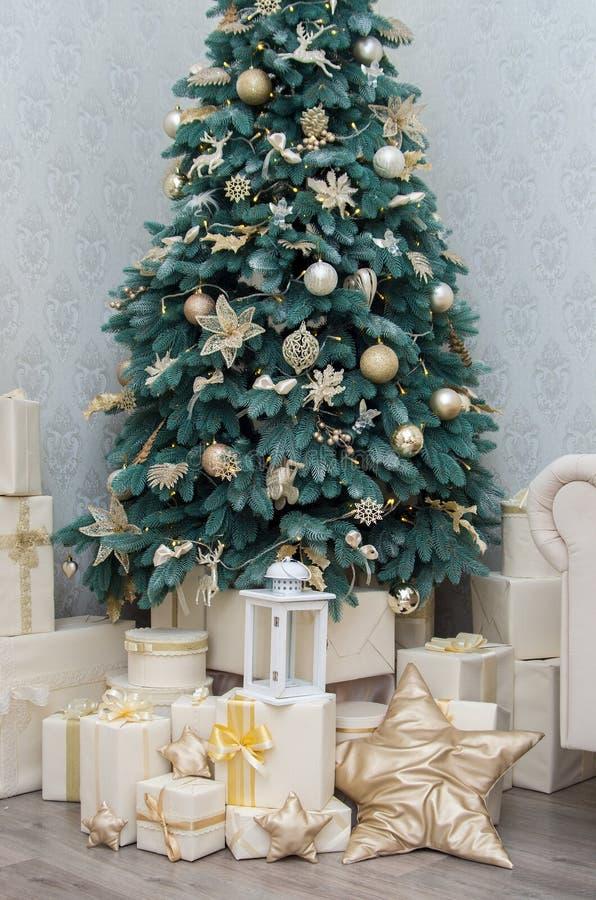 Cajas de regalos con una cinta del oro debajo de un árbol adornado imagen de archivo libre de regalías
