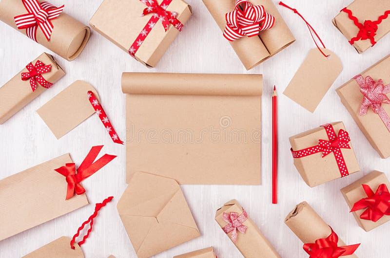 Cajas de regalos de la Navidad con las cintas rojas, la libreta en blanco y el lápiz rojo en el tablero de madera blanco como fon fotografía de archivo libre de regalías