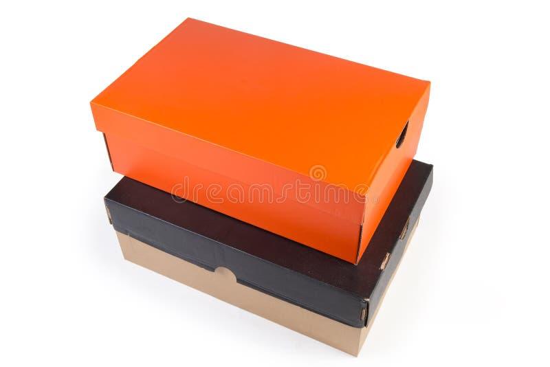 Cajas de zapatos negras y anaranjadas cerradas de la cartulina en el fondo blanco imagenes de archivo