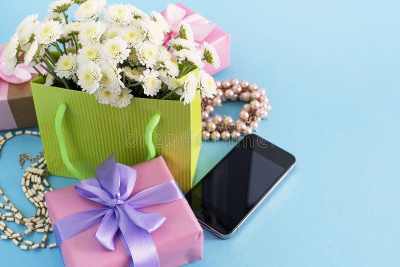 Cajas decorativas de la composición con las flores women' de los regalos; fondo del azul del día de fiesta de las compras de  foto de archivo libre de regalías