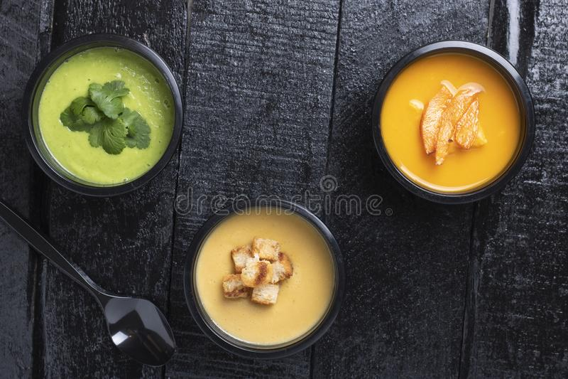 Cajas del almuerzo con avacado, la calabaza, la sopa de guisantes, la zanahoria y la pimienta en el tablero de la cocina, lugar p fotografía de archivo